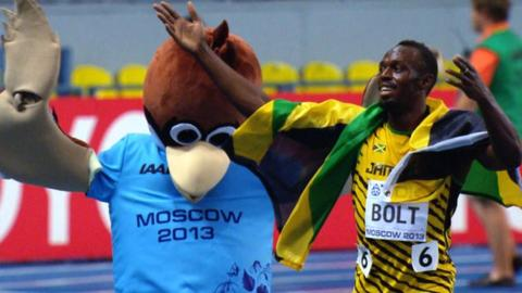 Usain Bolt celebrates with the official mascot of the World Championships