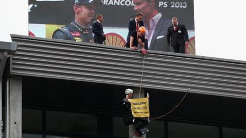 A protestor abseils from the roof to unveil a flag above the podium