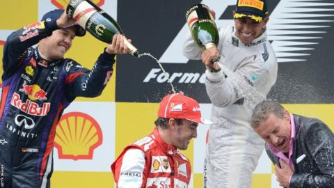 Sebastian Vettel (left) and Lewis Hamilton spray champagne on Ferrari's Spanish driver Fernando Alonso (second left) and David Coulthard on the podium