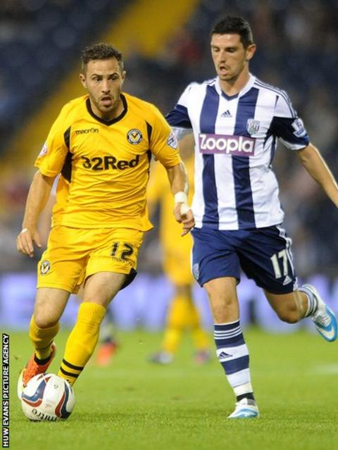 Graham Dorrans of West Bromwich Albion (right) right, chases Newport County's Robbie Wilmott in the Capital One Cup at The Hawthorns