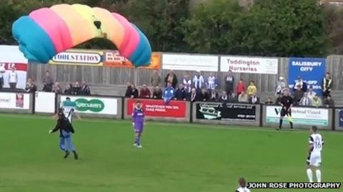 Parachutist landing on football pitch