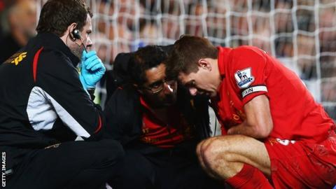 Steven Gerrard receives treatment from Zaf Iqbal on the pitch at Stamford Bridge