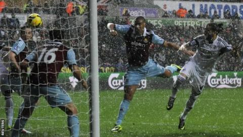 Swansea City's Chico Flores (right) heads an attempt on goal watched by West Ham United's Winston Reid (centre)