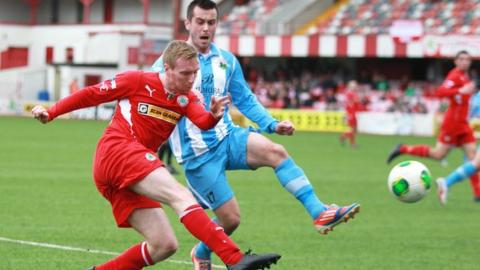 Chris Curran gets his cross in despite the presence of Warrenpoint's Mark Hughes
