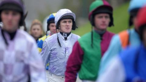 AP McCoy leaves the weighing room with colleagues ahead of a race