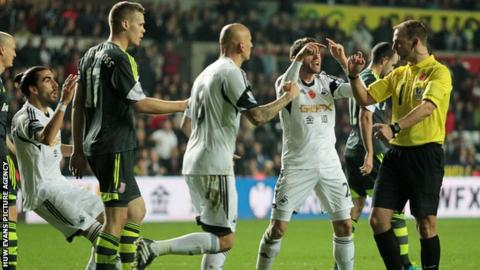 Swansea players show their disbelief after referee Robert Madley awards a late penalty to Stoke