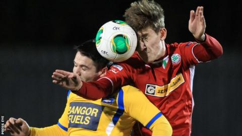 Dominic Melly goes for a high ball with Cliftonville's Paddy McNally