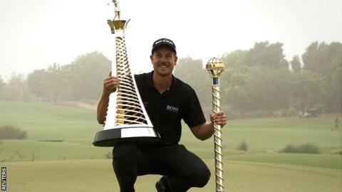 Henrik Stenson with the World Tour Championship and Race to Dubai trophies