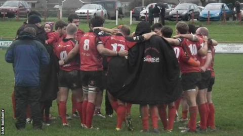 Redruth team in a post-match huddle.