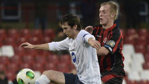 Howard Beverland and Jordan Owens contend for possession as Crusaders beat Coleraine 4-0