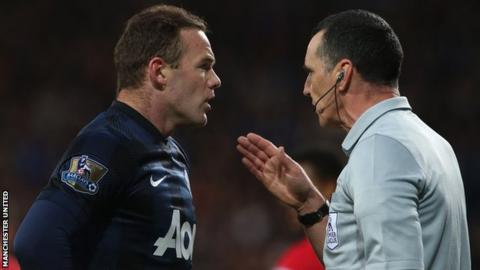 Manchester United striker Wayne Rooney makes a point to referee Neil Swarbrick after being booked against Cardiff