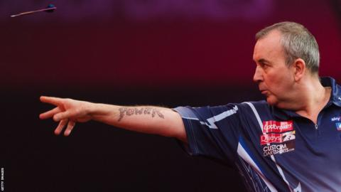 Phil Taylor taking part in the PDC World Championship darts final in January 2013