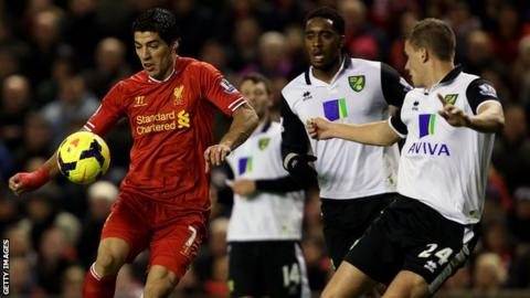 Luis Suarez of Liverpool eludes a host of Norwich City players