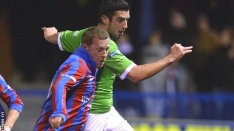 An Ards player challenges Cliftonville striker Joe Gormley