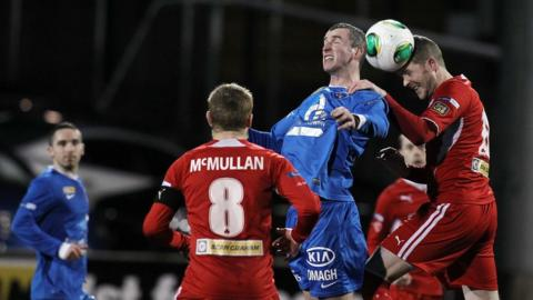 Ryan Campbell in aerial action with Marc Smyth at Solitude as Reds captain George McMullan looks on