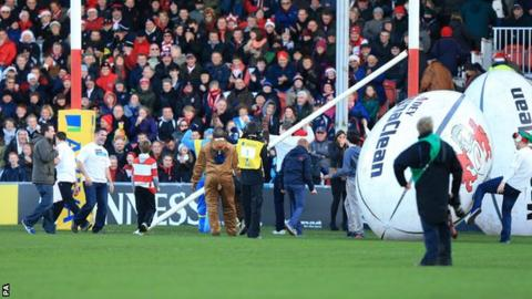Officials survey the damage after a giant rugby ball knocks off the crossbar before kick-off
