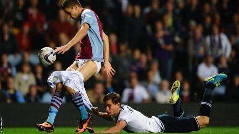 Tottenham defender Jan Vertonghen pulls down the shorts of Aston Villa's Nicklas Helenius as the striker is about to shoot during the Capital One Cup third round match at Villa Park. Spurs won the match 4-0.