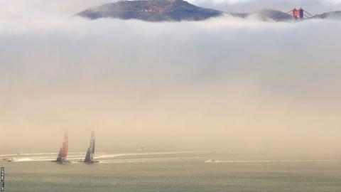 Emirates Team New Zealand races Oracle Team USA in front of the Golden Gate Bridge, mostly obscured by fog, during race three of the America's Cup. Oracle staged won of the greatest comebacks in sport to take the trophy, winning eight straight races to triumph 9-8.