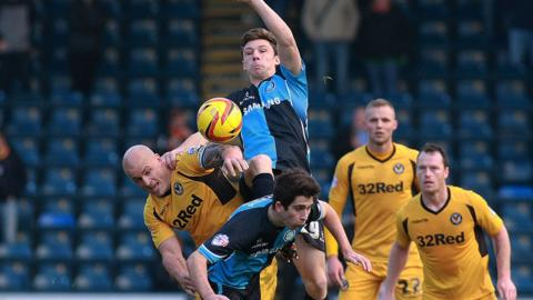 Newport County's David Pipe is beaten to the ball by Wycombe's Matt McClure at Rodney Parade