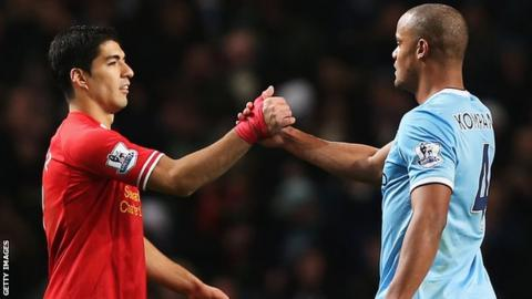 Liverpool's Luis Suarez shakes hands with Man City's Vincent Kompany
