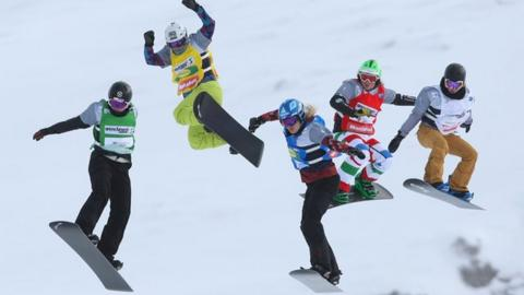 Athletes compete in the snowboard cross