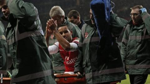 Theo Walcott is taken off on a stretcher