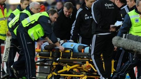 West Ham manager Sam Allardyce (centre) checks on the wellbeing of player Guy Demel who is stretchered off in the match at Cardiff