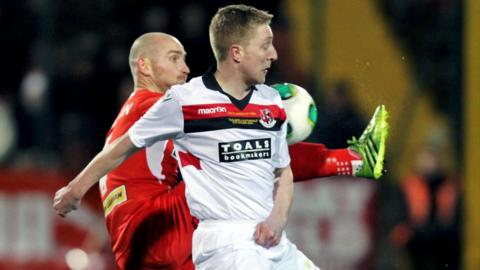Barry Johnston of Cliftonville competes against Crusaders opponent Chris Morrow during the League Cup final at Solitude