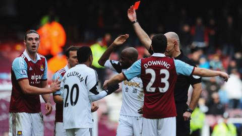 Andy Carroll receives a red card from Howard Webb after tangling with Swansea City's Chico Flores at Upton Park. The Hammers came out 2-0 winners