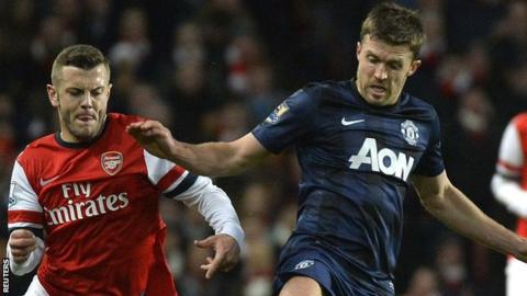 Arsenal midfielder Jack Wilshere and Manchester United midfielder Michael Carrick fight for the ball