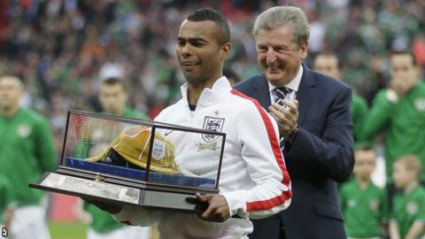 Ashley Cole, left, with a golden cap presented to him by manager Roy Hodgson, right, to mark his 100th cap for England.
