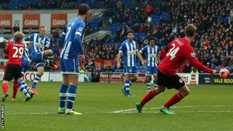 Wigan midfielder Ben Watson (second left) powers in a goal against Cardiff in their FA Cup tie