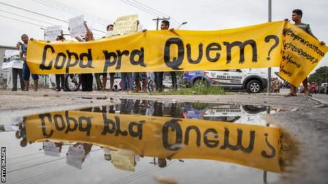 "Protestors outside the Amazonia Arena with a banner that reads ""World Cup for whom?"""