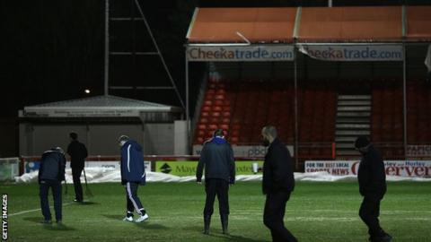 Crawley groundstaff inspect the pitch after the postponement
