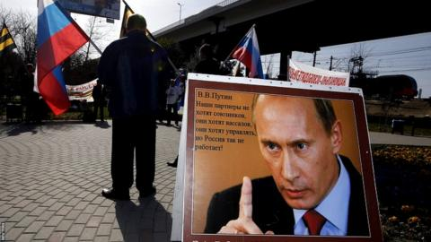 "A poster of Russian Vladimir Putin reading ""For Motherland, for Russia, for Sovereignty"" at a pro-government demonstration in Sochi."