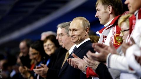 Russian President Vladimir Putin (C) stands during the Closing Ceremony of the Sochi Winter Olympic