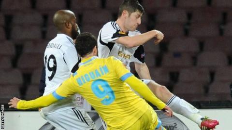 Gonzalo Higuain of Napoli scores despite the attention of Swansea defender Ben Davies