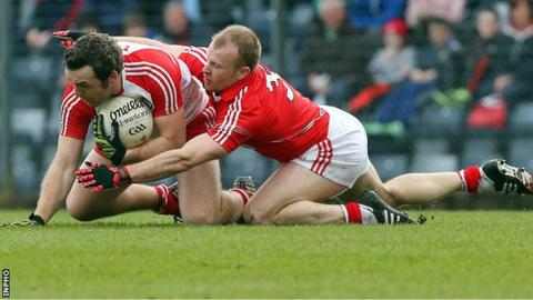 Derry's Emmet McGuckin holds on to possession as Michael Shields of Cork challenges