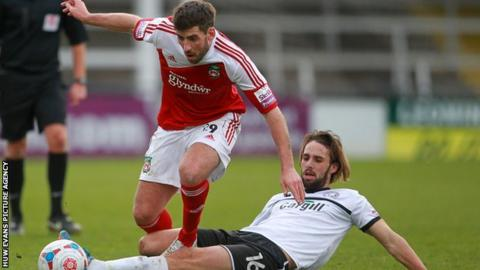 Mark Carrington of Wrexham is tackled by Frankie Artus of Hereford United
