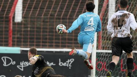 Alan Davidson lifts the ball over Declan Brown to score for Ballymena at the Oval