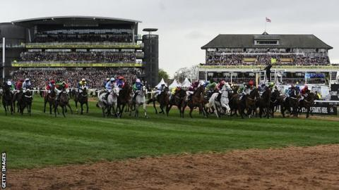The starter waves his flag to signal a false start in the Grand National