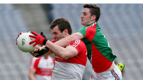 Prolific Derry points-scorer Mark Lynch attempts to shield the ball from Brendan Harrison