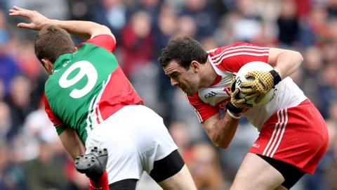 Jason Gibbons and Caolan O'Boyle in action during the first of Sunday's Football League Division One semi-finals