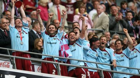 Burnley's Steven Caldwell (left) celebrates with the trophy and his team mates after gaining promotion into the Premier League in 2009