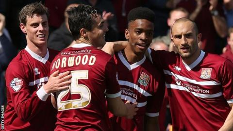 Northampton Town players celebrate scoring against Oxford United