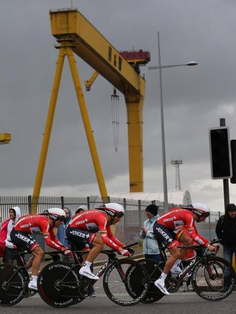 Members of the Belgian team Lotto Belison pass one of the famous Harland and Wolff shipyard cranes shortly after the team trial start at Titanic Quarter