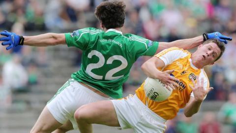 Fermanagh's Marty O'Brien sends Antrim opponent Thomas McCann crashing to the ground