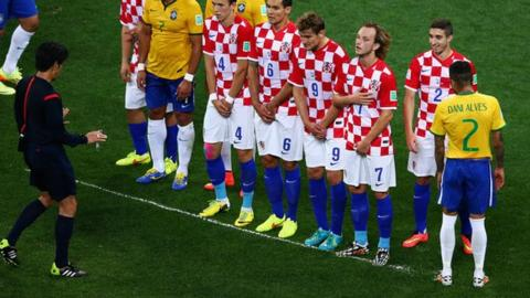 Referee Yuichi Nishimura uses vanishing spray during Brazil's win over Croatia