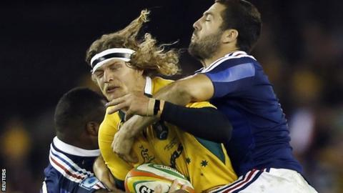 Australia's Nick Cummins is tackled by two French defenders