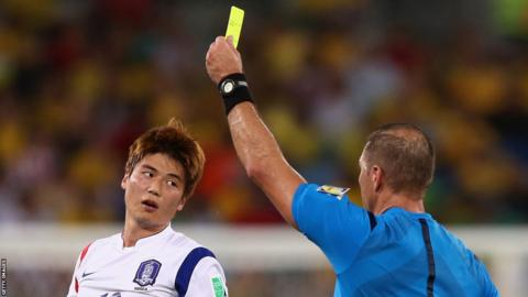 Swansea City's Ki Sung-Yueng of South Korea is shown a yellow card by referee Nestor Pitana during his country's 1-1 draw with Russia in Group H at the World Cup in Brazil.